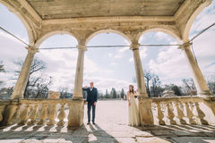 Wedding couple posing on arched terrace of antique ruined palace Royalty Free Stock Photo