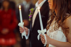 A wedding couple pray during an engagemnt ceremony holding candl. Es in their hands Stock Photography