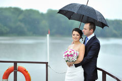 Wedding couple in a rainy weather on a boat Stock Image