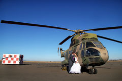 Wedding couple with retired military helicopter. Married couple, groom and bride, romantic moment, with vintage retired military helicopter,  clear blue skies Stock Photography