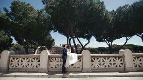 Wedding couple on romantic stone bridge in Rome, Italy. Stylish groom kissing with beautiful bride. Honeymoon in Italy. Europe stock video footage