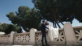 Wedding couple on romantic stone bridge in Rome. Stylish groom kissing with beautiful bride. Honeymoon in Italy, Europe.  stock footage