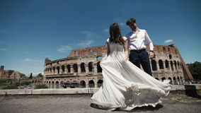 Wedding couple in Rome dancing barefoot at the rooftop near Coliseum, happy groom watches his bride playing with her