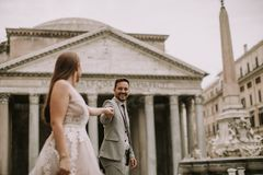 Wedding couple in Rome, Italy. Young attractive newly married couple walking  in Rome with beautiful and ancient architecture on the background on their wedding stock image