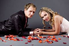 Wedding couple among rose petals Royalty Free Stock Images