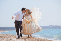 Wedding couple running on beach Royalty Free Stock Images
