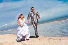 Wedding couple runs on the beach Stock Image