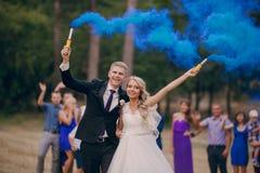 Wedding couple runs blue smoke Stock Photo