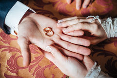 Wedding Couple's hands on the table and rings Royalty Free Stock Image