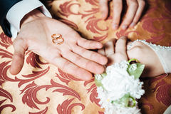 Wedding Couple's hands on the table and rings Stock Photos
