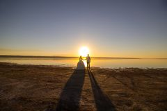 Wedding couple on the sea beach watching sunset. Sunny summer photo. Bride with hair down in off shoulder dress with train. Ocean royalty free stock photo