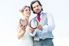 Wedding couple showing horse shoe for luck Stock Photo