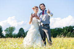 Wedding couple showing horse shoe. Wedding couple standing on a meadow in summer in the grass showing horse shoe stock photography