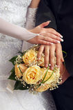 Wedding couple showing rings. On bouquet Royalty Free Stock Images
