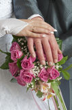 Wedding couple showing rings. A newly wed couple place their hands on a wedding bouquet showing off their wedding bands Royalty Free Stock Photos