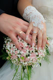 Wedding couple showing rings. A newly wed couple place their hands on a wedding bouquet showing off their wedding bands Stock Image