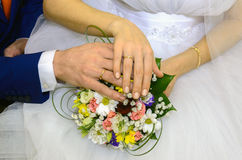 Wedding couple showing rings. A newly wed couple place their hands on a wedding bouquet showing off their wedding bands Royalty Free Stock Image