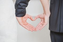 Wedding couple showing shape of heart from their Royalty Free Stock Photography