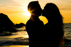 Wedding couple silhouette on the beach kissing. Stock Images