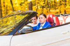 Wedding couple sits on a white cabriolet Royalty Free Stock Photography