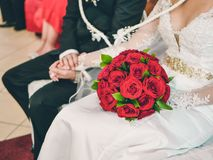 Wedding couple sitting in the church hand in hand with the bride holding a bouquet of red roses royalty free stock photos