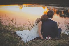 Wedding Couple Sitting on Green Grass in Front of Body of Water at Sunset Royalty Free Stock Images