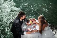 Wedding couple sitting and hugging at the decorate. D table and celebrating their marriage on the river Stock Photo