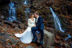 Wedding couple sitting on stone and lovingly look at each other. Waterfall background. Royalty Free Stock Photography