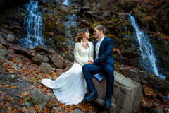 Wedding couple sitting on stone and lovingly look at each other. Waterfall background Stock Image