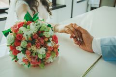 Wedding couple is sitting at th restaurant table and holding hands. wedding details. Bouquet, manicure and hand watch. Romance and stock photos