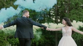 Wedding couple spin together color smoke in the park. Slow motion. Wedding couple runs color smoke in the park. Colour bomb. kiss and hug stock video footage
