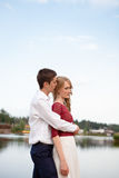 Wedding couple standing and hugging near lake Stock Image
