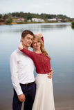 Wedding couple standing and hugging near lake Stock Photos