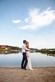 Wedding couple standing and hugging near lake Royalty Free Stock Images