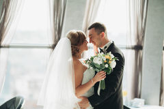Wedding couple is standing and kissing in hotel Stock Photos
