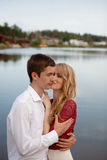 Wedding couple standing and kissing near lake Stock Images