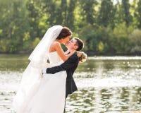 Wedding couple standing and kissing near lake. Stock Photo