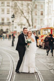 Wedding couple is standing and kissing in the streets of old city Stock Photos