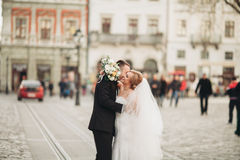 Wedding couple is standing and kissing in the streets of old city Royalty Free Stock Photos