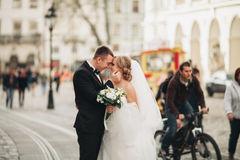 Wedding couple is standing and kissing in the streets of old city Royalty Free Stock Image