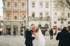 Wedding couple is standing and kissing in the streets of old city Royalty Free Stock Photography