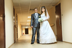 Wedding couple standing in long corridor Stock Images
