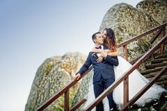 Wedding couple standing in the mountains against the sky. Cute r Royalty Free Stock Images