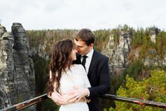 Wedding couple standing in the mountains against the sky. Cute romantic moment. Best day in the life of the bride. royalty free stock images