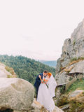 Wedding couple standing at rocky mountains against the sky and kissing. Cute romantic moment. Stock Images