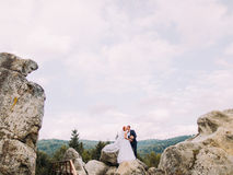 Wedding couple standing at rocky mountains against the sky and kissing. Cute romantic moment. Stock Photos
