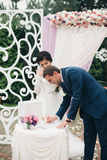 Wedding couple standing under an arch of fresh flowers.  Royalty Free Stock Photos