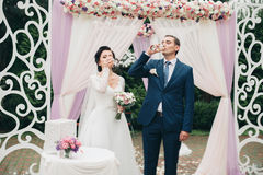 Wedding couple standing under an arch of fresh flowers.  Stock Image