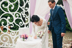 Wedding couple standing under an arch of fresh flowers.  Royalty Free Stock Images