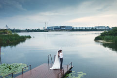 Wedding couple stands on the berth of river with an industrial b Royalty Free Stock Image
